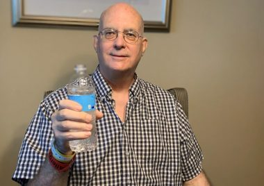 Kevin toasts to his discharge with a bottle of water. / Pulmonary Fibrosis News
