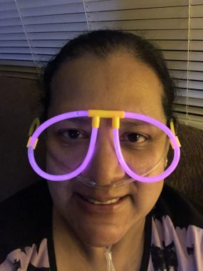Columnist Ann Reynoso smiles while wearing neon purple glowstick glasses and oxygen.